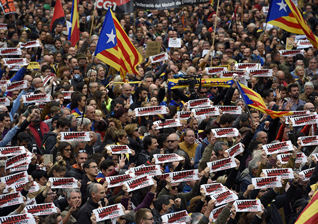 People hold placards reading Free political prisoners and Catalan pro-independence 'Estelada' flags during a demonstration outside the Generalitat Palace in Barcelona on November 8, 2017 during a regionwide strike called by a pro-independence union