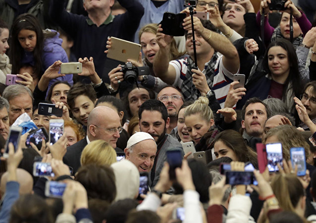 People photograph and film Pope Francis with their smartphone as he arrives for his weekly general audience in Paul VI Hall at the Vatican, Wednesday, Dec. 21, 2016