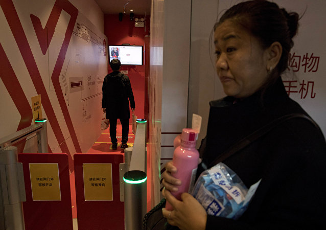 A woman waits to leave a Unmanned Convenience Store that uses facial recognition to allow shoppers to walk in and pay for their purchases without having to go through a human cashier at the headquarters forChinese e-commerce giant JD.com in Beijing, China, Saturday, Nov. 11, 2017. Chinese consumers are spending billions of dollars shopping online for anything from diapers to diamonds on Singles Day, a day of promotions that has grown into the world's biggest e-commerce event.