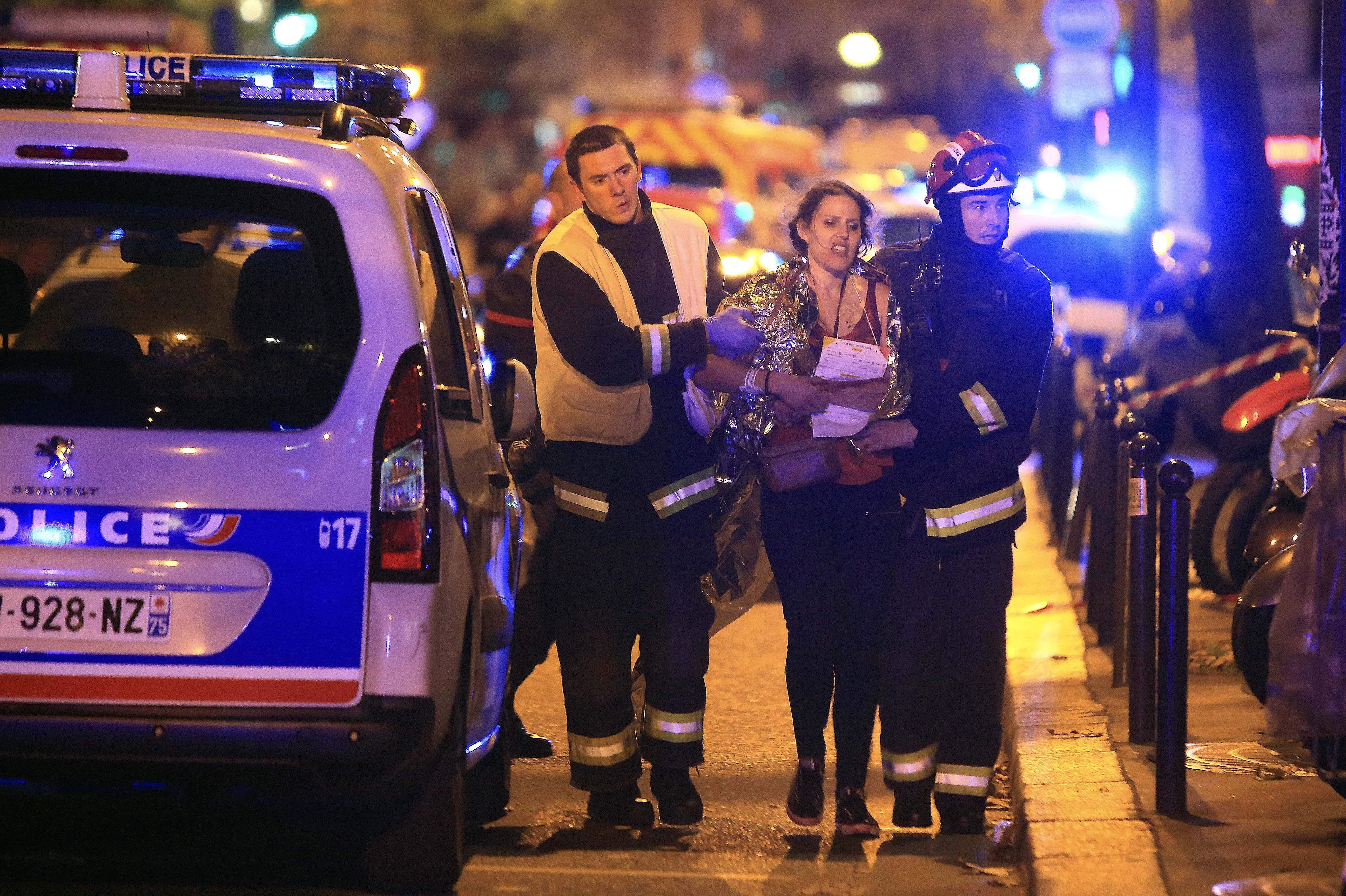 Rescue workers help a woman after a shooting, outside the Bataclan theater in Paris, Friday Nov. 13, 2015.