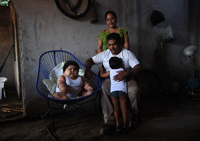 Ten-month-old Luis Gonzales (L) is pictured with his parents Isabel Pantoja (standing) and Mario Gonzales, and his elder brother Mario at their home in Tecoman, Colima State, Mexico on November 8, 2017