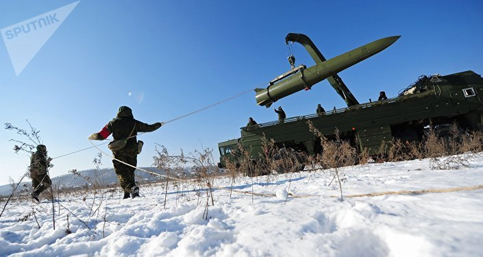 Russian soldiers watch a transporter-loader place an Iskander-M shorter-range missile onto a launcher during an exercise
