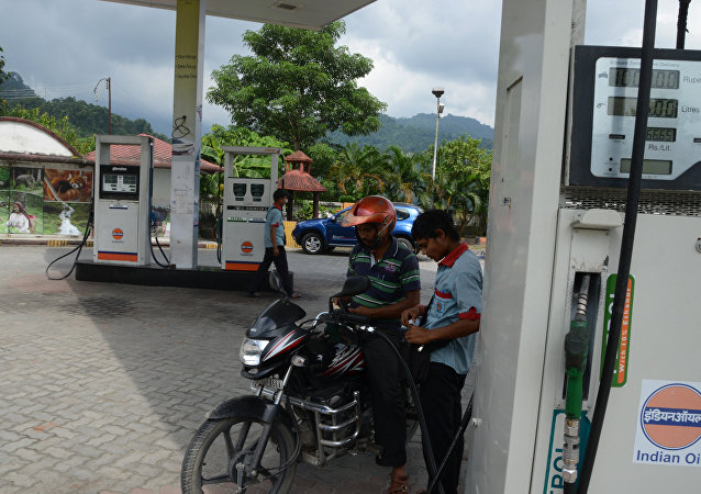 An Indian fuel station attendant serves a customer at a petrol pump at Sevok Bazar, some 24km from Siliguri, on September 29, 2016