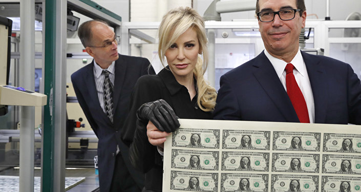 Treasury Secretary Steven Mnuchin, right, and his wife Louise Linton, hold up a sheet of new $1 bills, the first currency notes bearing his and U.S. Treasurer Jovita Carranza's signatures, Wednesday, Nov. 15, 2017, at the Bureau of Engraving and Printing (BEP) in Washington.