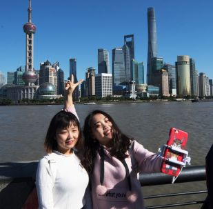 People take a selfie against the backdrop of the Lujiazui skyline, seen from the Bund, across the Huangpu River