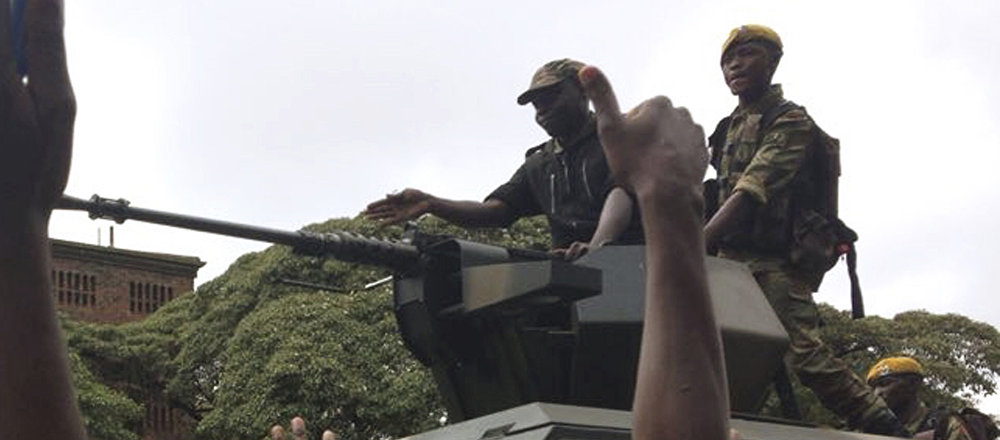 People begin to gather around a military vehicle in Harare Saturday, Nov. 18, 2017, demonstrating for the ouster of 93-year-old president Robert Mugabe who is virtually powerless and deserted by most of his allies