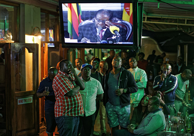 Zimbabweans watch a televised address to the nation by President Robert Mugabe at a bar in downtown Harare, Zimbabwe Sunday, Nov. 19, 2017