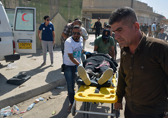 Members of the Iraqi Counter-Terrorism Service (CTS) carry an elderly woman into an ambulance prior to being transported to a hospital (File)