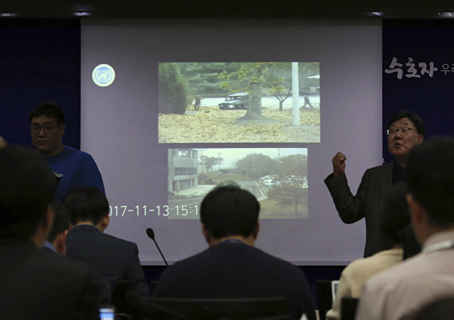 Journalists watch CCTV footage regarding a North Korean soldier's defection, during a press conference at the Defense Ministry in Seoul, South Korea, Wednesday, Nov. 22, 2017