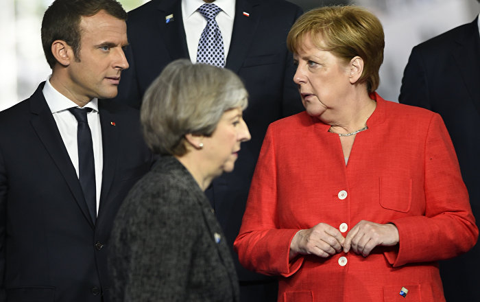 Britain's Prime Minister Theresa May, foreground walks by French President Emmanuel Macron, left, and German Chancellor Angela Merkel as they gather with NATO member leaders to pose for a group photo, prior to the start of their summit in Brussels, Belgium, Thursday, May 25, 2017.