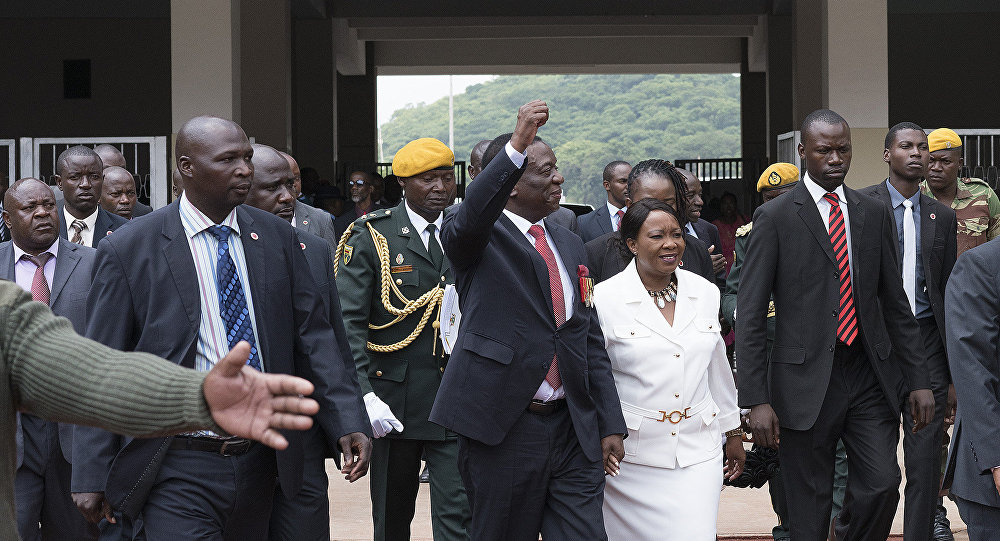 President elect Emmerson Mnangagwa (C,L) gestures as he arrives with his wife Auxilia (C,R) at the National Sport Stadium in Harare, on November 24, 2017 during the Inauguration ceremony