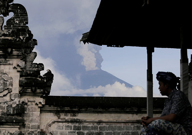 A Balinese man sits as Mount Agung volcano erupts at Lempuyang Temple in Karangasem, Bali, Indonesia November 27, 2017