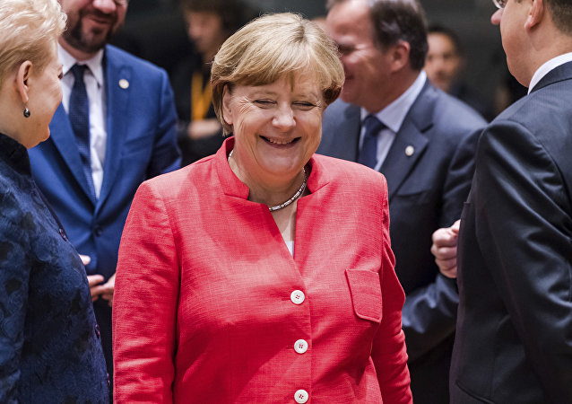 German Chancellor Angela Merkel, center, smiles as she attends a round table meeting at an EU Summit in Brussels on Friday, June 23, 2017.