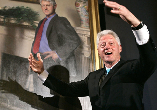 Former President Bill Clinton, gestures after the portraits of his wife Hillary Rodham Clinton and him were revealed