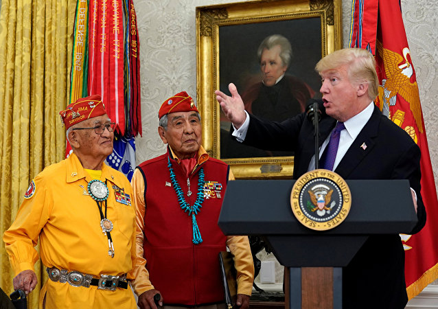 U.S. President Donald Trump gestures as he hosts an event honouring the Native American code talkers, including Thomas Begay (L) and Peter McDonald, in front of a painting of President Andrew Jackson, at the White House in Washington, U.S., November 27, 2017.