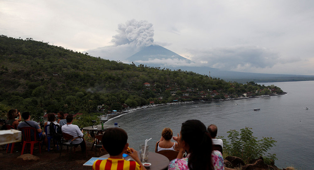 People watch Mount Agung volcano erupt from a cafe near Amed, Karangasem Regency, Bali, Indonesia November 28, 2017