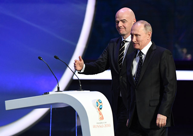 Russian President Vladimir Putin (R) is welcomed on stage by FIFA president Gianni Infantino during the 2018 FIFA World Cup football tournament final draw at the State Kremlin Palace in Moscow
