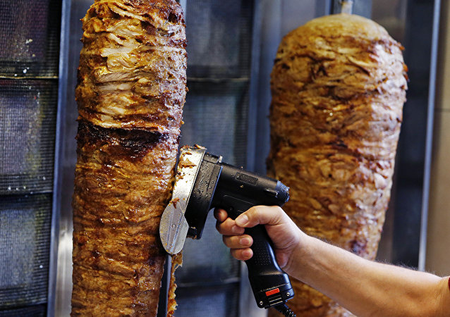 A man slices cuts of meat from a rotisserie Doner spit inside a Doner restaurant in Frankfurt, Germany, Thursday, Nov. 30, 2017