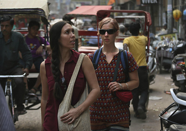 In this Tuesday, April 2, 2013 photo, foreign tourists walk on a street near the railway station in New Delhi, India