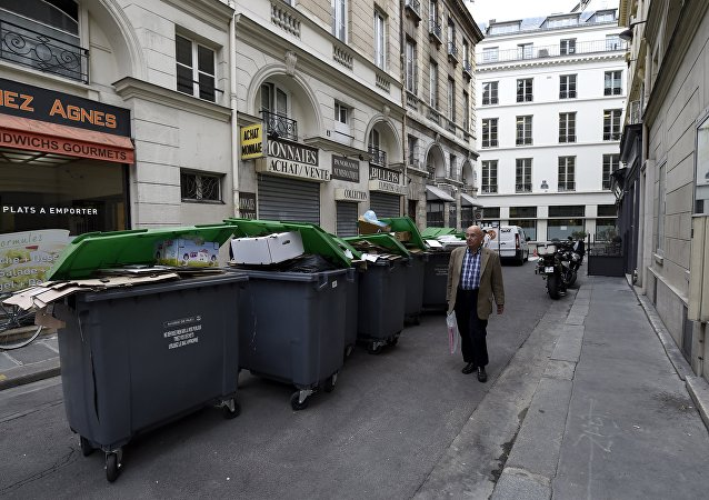 (File) A pedestrians walks past unemptied garbage bins and plastic bags during a strike of garbage collectors in a street in Paris on October 8, 2015