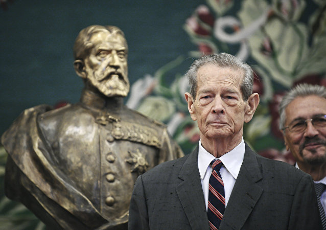 Former Romanian King Michael poses next to a bronze sculpture depicting the founder of Romania's royal dynasty, King Carol I, in the country's parliament in Bucharest, Romania