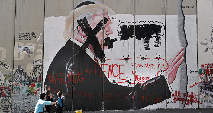 Palestinian children look at vandalised graffiti depicting US President Donald Trump and slogans against US Vice President Mike Pence painted on Israel's controversial separation barrier in the West Bank city of Bethlehem during clashes with Palestinian protestors near an Israeli checkpoint on December 7, 2017