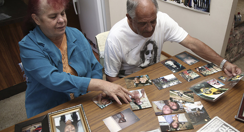 In this Aug. 15, 2016 photo, Gordon Davis and his wife Thelma look through photos of their daughter, Lynette Daley, at their home in Yamba, Australia. The brutal death of Daley, an Aboriginal woman, and the reluctance of officials to prosecute the white suspects, has highlighted a deadly racial divide in Australia, where Indigenous people remain the most disadvantaged segment of society