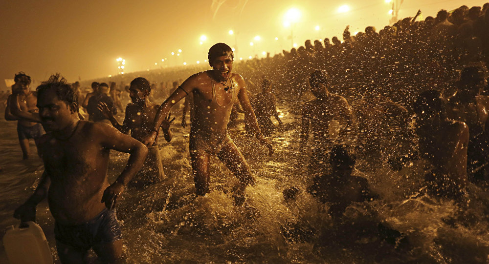In this Jan. 14, 2013 file photo, an Indian Hindu man jumps up and down in the water as he takes a dip at Sangam, the confluence of the Ganges, Yamuna and mythical Saraswati River, during the royal bath on Makar Sankranti at the start of the Maha Kumbh Mela in Allahabad, India