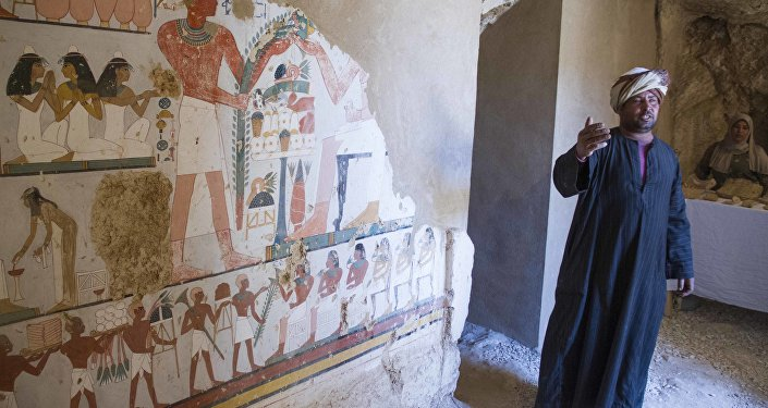 An Egyptian guard stands next to a funeral mural inside a newly discovered tomb on Luxor's West Bank known as KAMPP 161 during an announcement for the Egyptian Ministry of antiquities about new discoveries in Luxor, Egypt, Saturday, Dec. 9, 2017