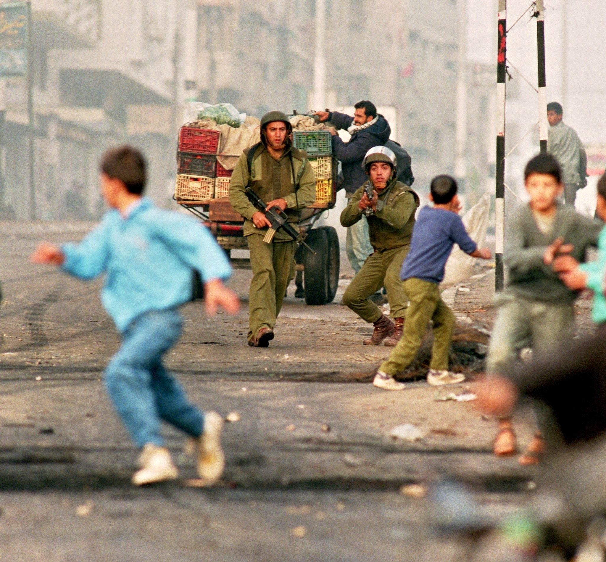 Palestinian youngsters flee Israeli soldiers during riots 26 November 1993 in Gaza City