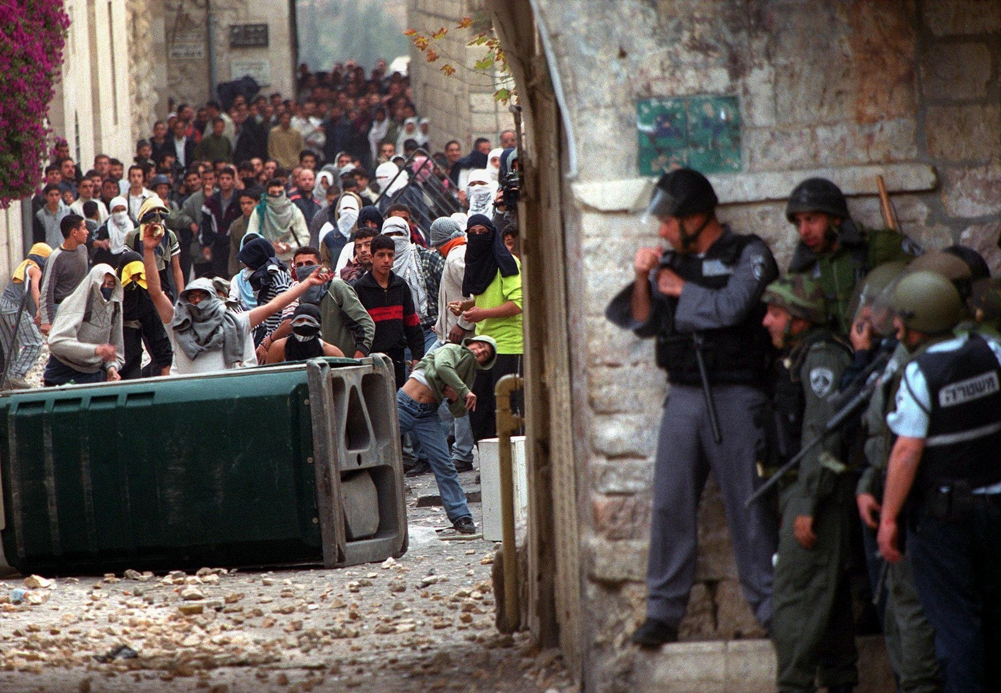 Israeli borderguards take cover from Palestinian stone-throwers in Jerusalem's Old City outside the al-Aqsa mosque compound 08 December 2000, as clashes erupted following the second Friday noon prayer in the holy month of the Ramada