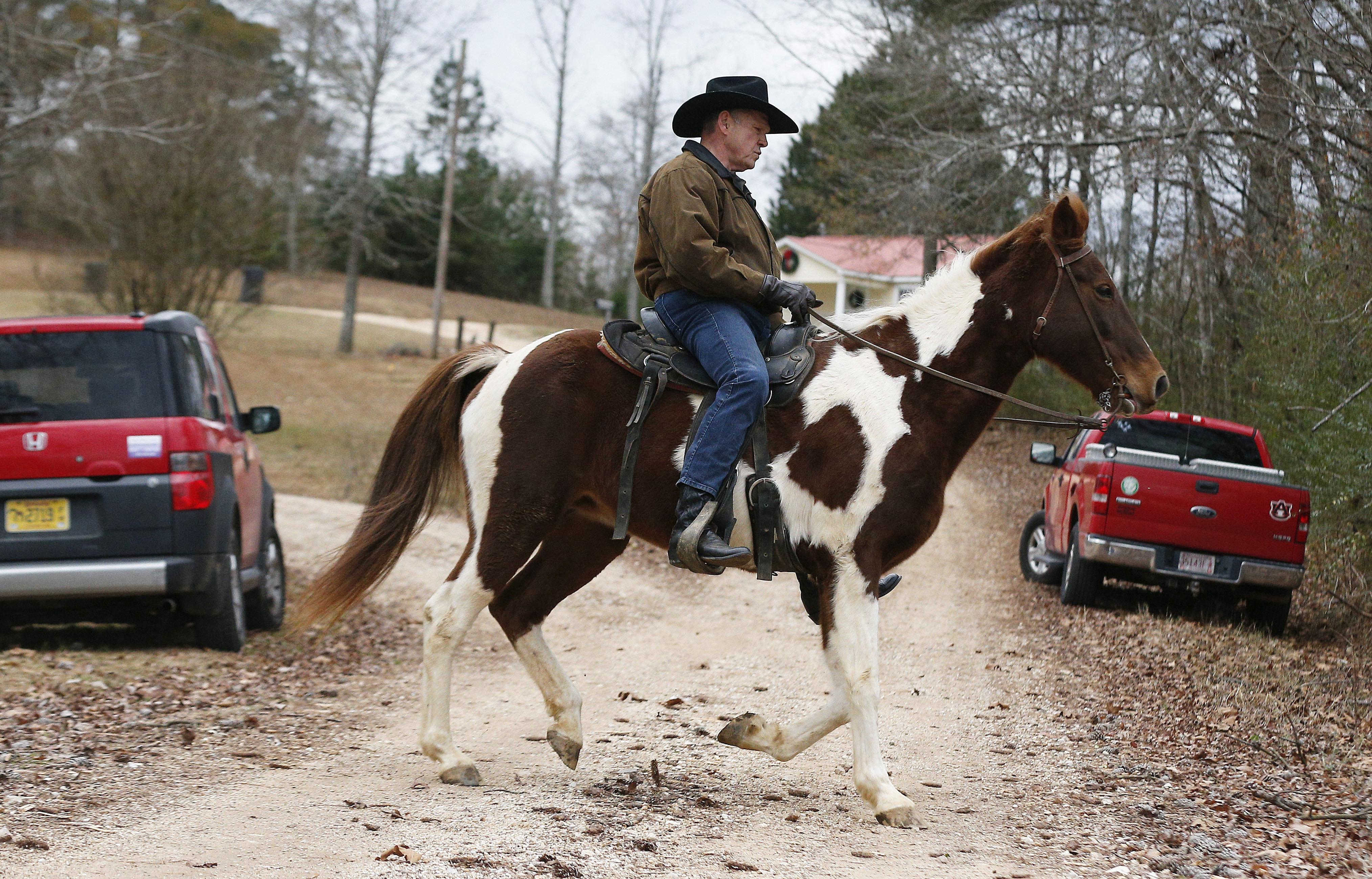 U.S. Senate Republican candidate Roy Moore rides a horse to vote, Tuesday, Dec. 12, 2017, in Gallant, Ala.