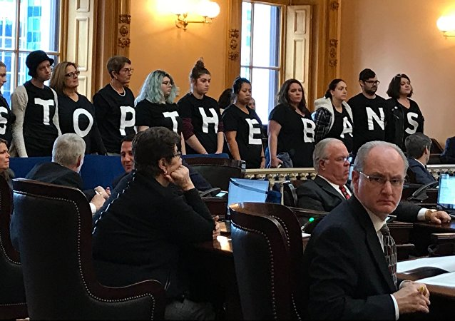 Abortion-rights activists stand in protest on Wednesday, Dec. 13, 2017, in the Ohio Senate chamber in Columbus, after passage of a bill banning abortions in cases of a Down syndrome diagnosis