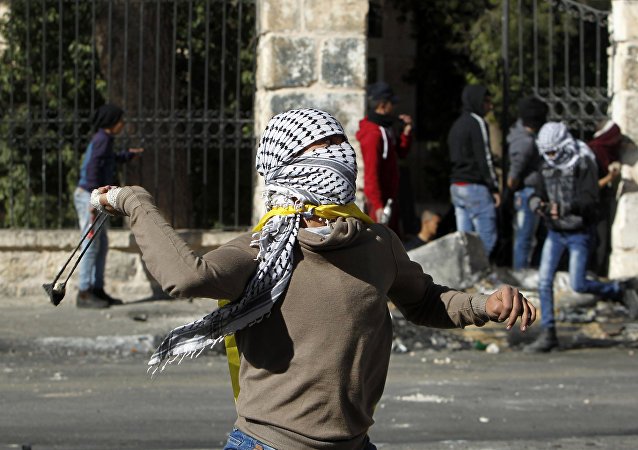 A Palestinian protestors throws a rock towards Israeli security forces during clashes at the main entrance of the occupied West Bank town of Bethlehem