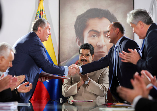 Head of Russian state oil firm Rosneft Igor Sechin (standing L) shakes hands with Venezuela's Oil Minister and President of the Venezuelan state oil company PDVSA Manuel Quevedo, in front of Venezuela's President Nicolas Maduro, in Maiquetia, Venezuela December 16, 2017.