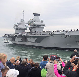People watch as Britain's new flagship HMS Queen Elizabeth arrives in Portsmouth, Britain, Wednesday Aug. 16, 2017