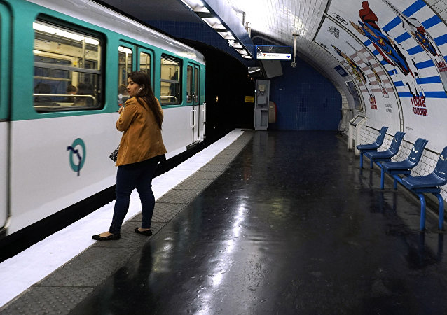 A woman waits the metro on the platform, next to a play on words made with the Jussieu metro station, reading I'm here to stay, in Paris, on April 1, 2017