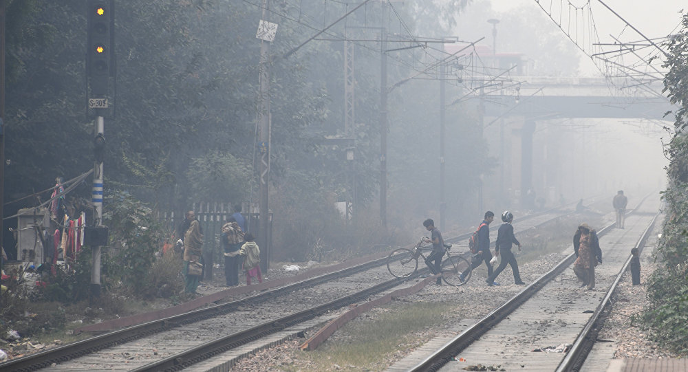 Indian residents walk amid heavy smog near the Lodhi railway station in New Delhi
