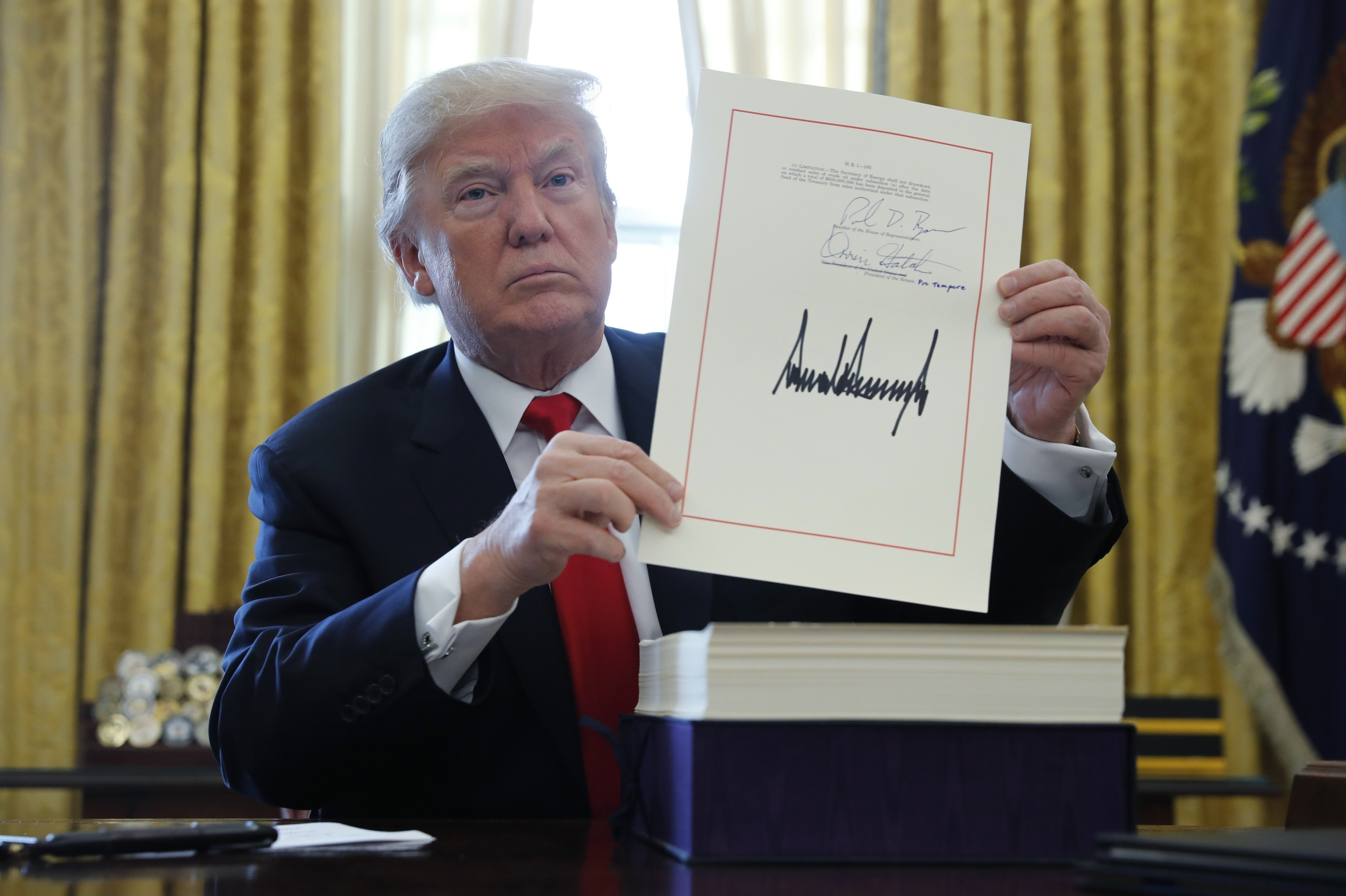 U.S. President Donald Trump displays his signature after signing the $1.5 trillion tax overhaul plan along with a short-term government spending bill in the Oval Office of the White House in Washington, U.S