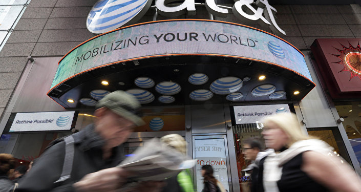In this Oct. 21, 2014 photo, people pass an AT&T store in New York's Times Square. AT&T is being sued by the government over allegations it misled millions of smartphone customers who were promised unlimited data but had their Internet speeds cut by the company — slowing their ability to open web pages or watch streaming video.