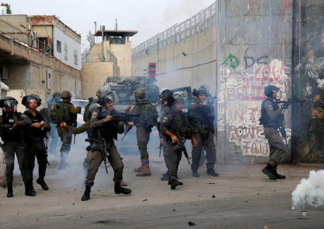An Israeli border policeman fires tear gas canisters at Palestinian demonstrators during clashes in the West Bank city of Bethlehem, December 23, 2017