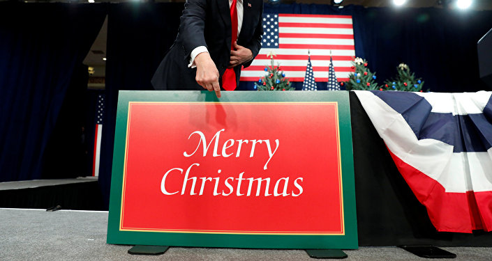 U.S. President Donald Trump points to a large Merry Christmas card on the stage as he arrives to deliver remarks on tax reform in St. Louis Missouri