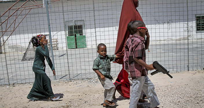 In this photo taken Saturday, Oct 4, 2014, a Somali mother walks with her children, one carrying a plastic toy gun, towards an area with children's toys to play with at the Mogadishu Guest House, in Mogadishu, Somalia