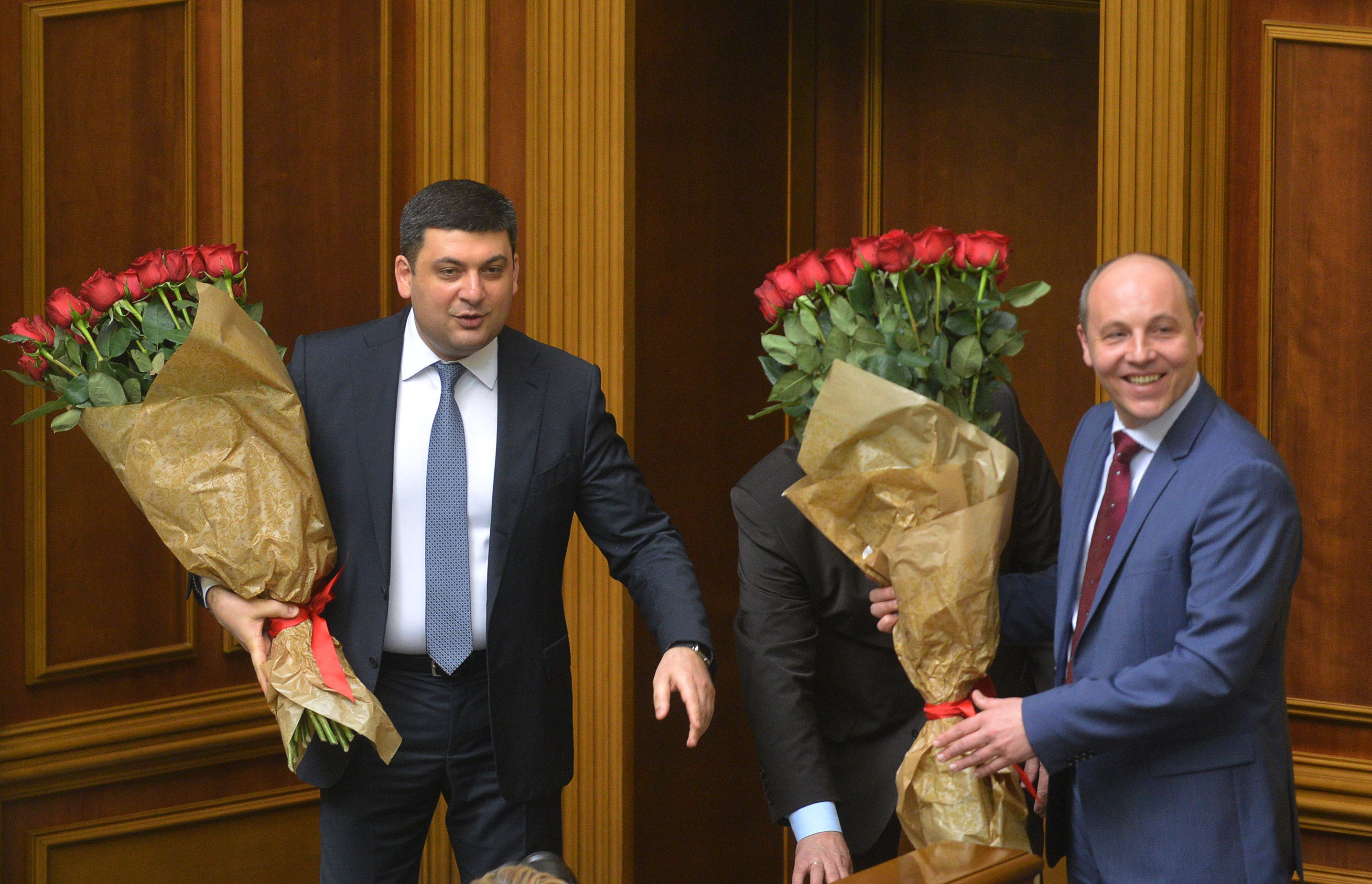 Ukrainian Prime Minister Volodymyr Groysman (L) and Andriy Parubiy, chair of the Ukrainian Parliament, hold bouquets of red roses during a parliamentary session in Kiev on April 14, 2016