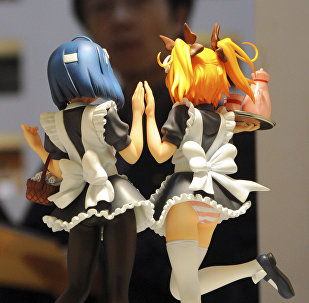 A visitor to the Tokyo International Anime Fair looks at cartoon figures on display in Tokyo (File)