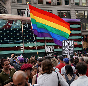 A rainbow flag flies as people protest U.S. President Donald Trump's announcement that he plans to reinstate a ban on transgender individuals from serving in any capacity in the U.S. military, in Times Square, in New York City, New York, U.S., July 26, 2017.