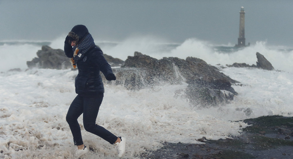 A woman runs as waves crash against the seafront in Auderville, Normandy, as storm Eleanor hits the northern part of France on January 3, 2018