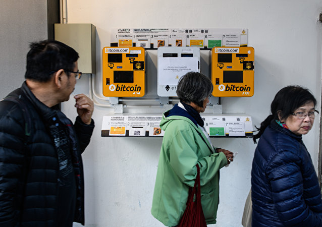 Pedestrians walk past ATM machines (L and R) for digital currency Bitcoin in Hong Kong on December 18, 2017