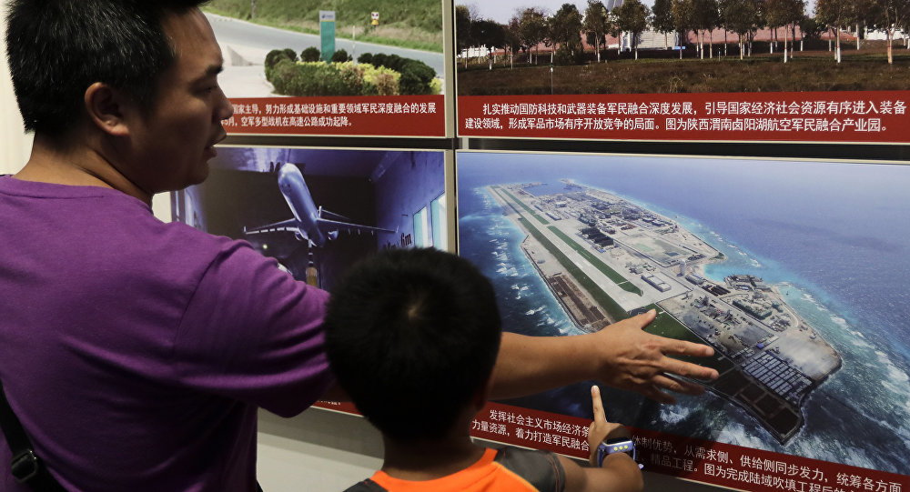 In this Thursday, July 27, 2017, file photo, a man and a child look at a picture showing the Fiery Cross Reef in the Spratly islands, in the disputed South China Sea, on display at the military museum in Beijing