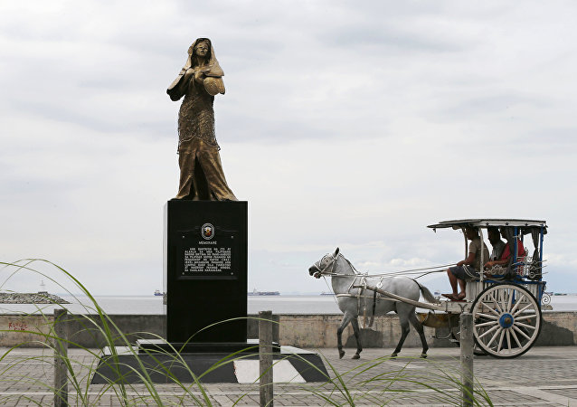 A horse-drawn cart, catering to tourists, passes by a statue of a Comfort Woman or Filipino sex slaves during WWII, which was erected along a scenic Baywalk in Manila, Philippines Thursday, Jan. 11, 2018